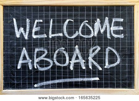 The words Welcome Aboard written by hand on a blackboard as an invitation or message to a new employee or partner