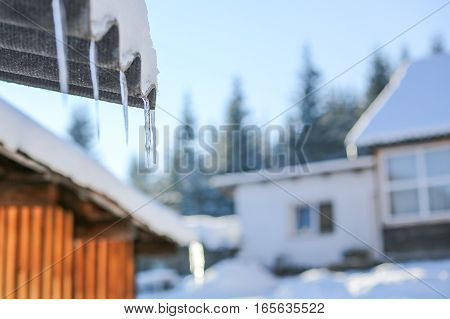 Close-up With Icicles On A Wooden Mountain House On A Sunny Day
