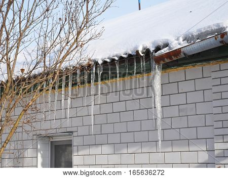 Bad old metal rain gutter and icicles