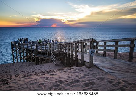Empire, Michigan, USA - August 22, 2016: Tourists admire a Lake Michigan sunset from overlook #9 in the Sleeping Bears Dune National Lakeshore.