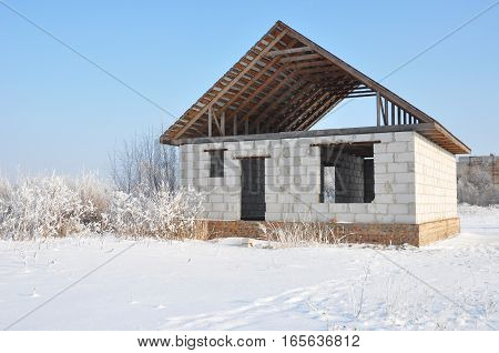 Building a Home During Winter. Building new house from autoclaved aerated concrete blocks vs bricks with unfinished roofing metal tiles construction.