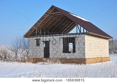 Building new house from autoclaved aerated concrete blocks vs bricks with unfinished roofing metal tiles construction. poster