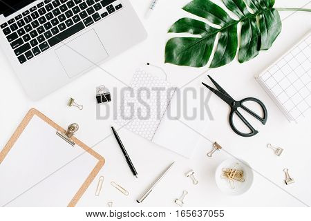 Home office workspace with laptop clipboard palm leaf notebook and accessories. Flat lay top view
