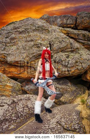 Beautiful female character with two swords near the big stones in mountain area. Fashion model girl cosplay character