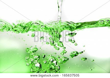 Green lit water splash with bubbles on bright background.