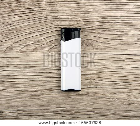 White lighter on a wooden background, close up