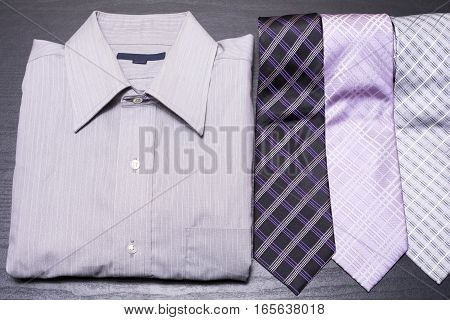 Lined shirt and ties on black desk