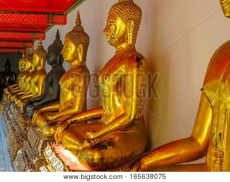 BANGKOK, THAILAND - JANUARY 16, 2014: Statues of the sitting Buddha in the Wat Pho Temple or Temple of the Reclining Buddha Bangkok Thailand