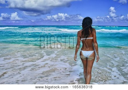 Girl in white swimsuit on the sea background from the back