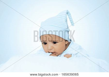 Adorable Six Month Baby Boy Wearing Blue Suite In White Bedding
