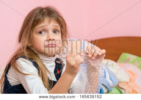 Upset Girl Pouting Cheeks Eats Bubbles Packaging Film And Looked For Someone