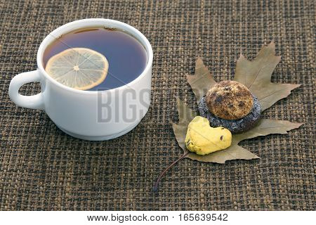 white cup of tea with lemon and biscuits