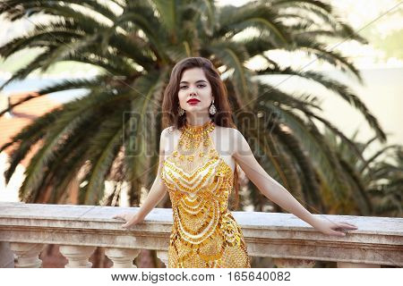 Woman Luxury Life. Fashionable Sexy Girl Model In Luxury Golden Dress. Beautiful Young Brunette With