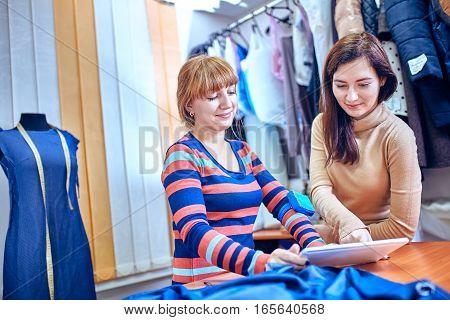 Fashion designer using tablet computer in studio