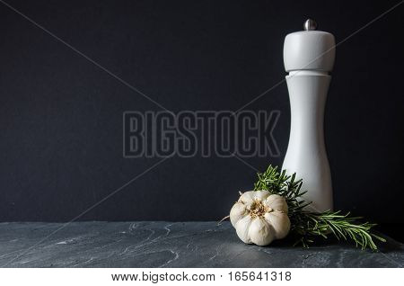 Modern salt  wooden grinder painted white with garlic cloves and rosemary branches on grey stone surface and black background. Concept or metaphor for healthy lifestyle and cooking.