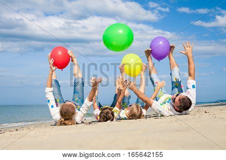 Happy Family Playing With Balloons On The Beach At The Day Time.
