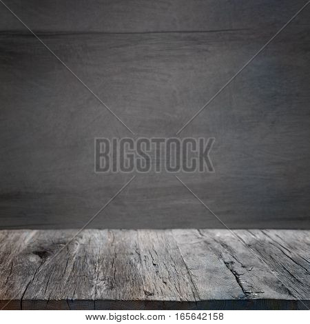 Dark gray background in front of a wooden stage