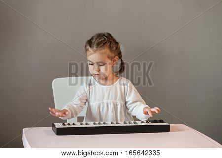 Cute little girl in white shirt playing electronic piano. Process of education cognition
