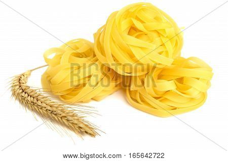 Pasta tagliatelle in a nest and spikelet wheat isolated on white background. Close-up.
