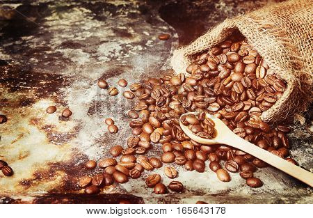 Roasted Coffee Beans In Small Sack On Metal Surface