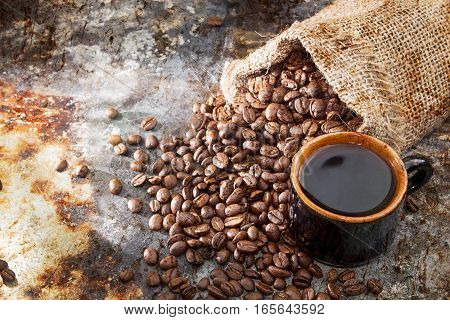 Roasted Coffee Beans In Small Sack And Cup Of Coffee