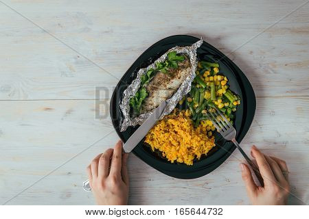 plate with rise fish and vegetables with woman hands