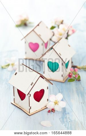 White Wood houses with colorful heart shaped windows.