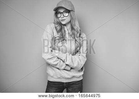 Portrait of a cute positive blonde woman in a pink baseball cap glasses and sweatshirt on bright background in studio