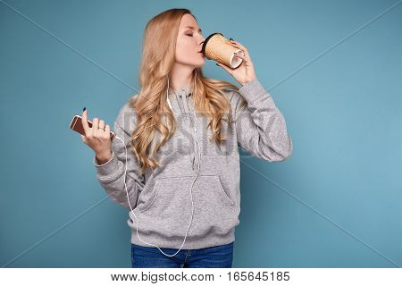 Cute Positive Blonde Woman In Hoodie With Phone And Coffee