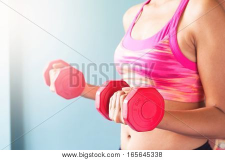 Woman in pink sport bra holding red dumbbells. Workout concept