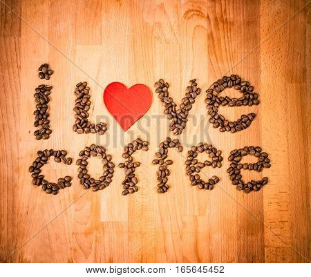 Coffee beans on wood background. Shape of words I Love Coffee made from coffee beans, decorated with red heart on wooden surface. Roasted coffee beans on rustic wood background. Top view. Copy space.