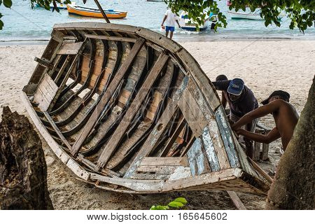 Tamarin Mauritius - December 8 2015: Unidentified villagers repair wooden boat on shore at Tamarin Bay in Mauritius.