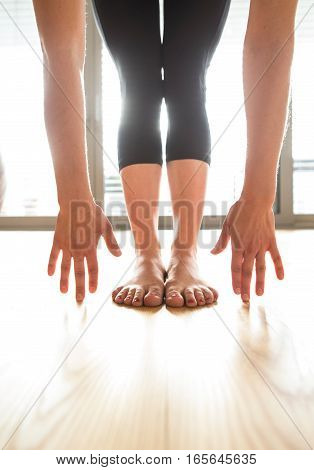 Unrecognizable young woman working out at home in living room, doing yoga or pilates exercise, stretching legs and arms.