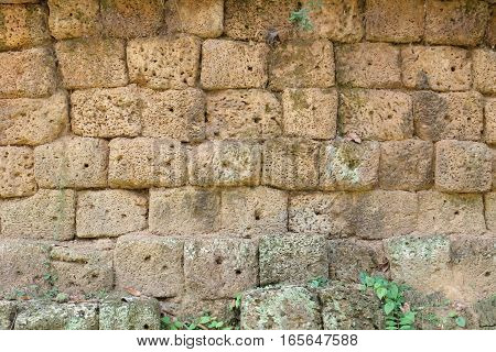 A wall made of volcano stone blocks. Each cube is rectangle or square with an irregular shape and porous surface. This ancient wall is part of the overgrown and long lost ruins of the sunken city Angkor in Cambodia.