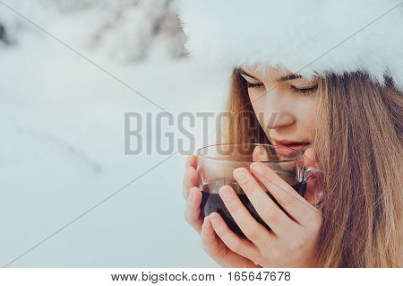 Girl with a cup of tea in the winter forest
