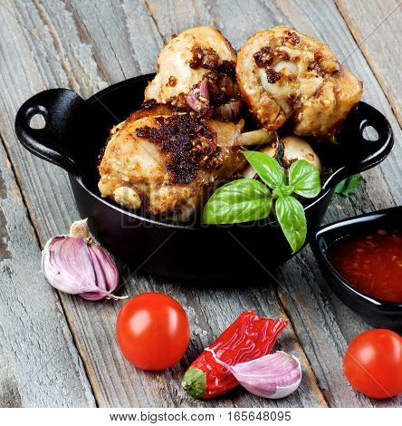Delicious Spicy Roasted Chicken Legs in Black Frying Pan with Ingredients and Sauce closeup on Rustic Wooden background