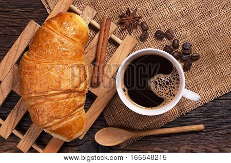 Cup of coffee and croissant on rustic wooden table top