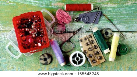 Arrangement of Various Pins Rivets Needles Thread Spools and Scissors closeup on Cracked Wooden background. Top View