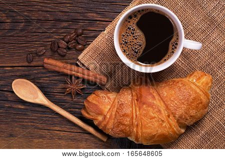 Cup of coffee with croissant on old wooden table top view