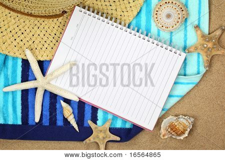 Vacation memory from beach,notebook,starfish,straw hat and towel on sand beach.