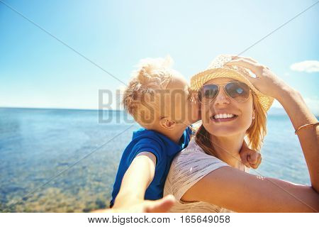 Woman Holding Boy On Back Kissing Her