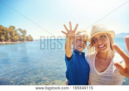 Cute Little Boy Waving At The Camera On A Beach
