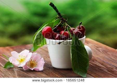 Fresh cherries in bowl on table. Fresh cherries in pot on the table. Cherries with leaves on a wooden board