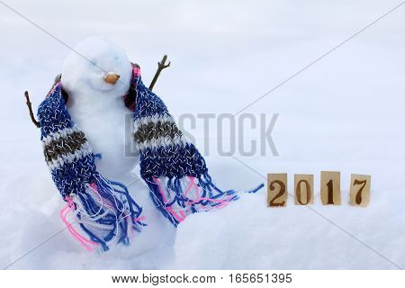 smiling snowman in the scarf next to numbers in the snowdrift / happy winter vacation