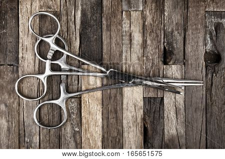 Surgical instrument. Stainless steel forceps on wooden background. Macro shot.
