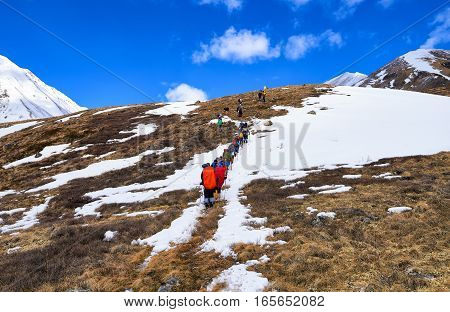 MUNCH-SARDYK BURYATIA RUSSIA - April 30.2016: Climbers on hillside in front of approach to foot of mountain. Active holidays in Eastern Sayan
