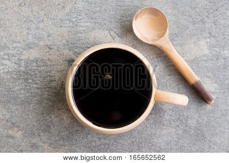 a cup of espresso coffee and wooden spoon