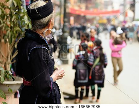 Woman in the traditional dress of Black Homong looking to the street in the Sapa town Vietnam