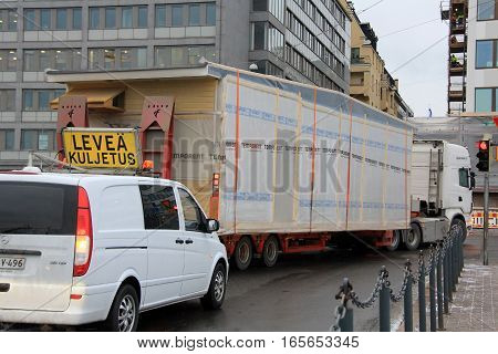HELSINKI, FINLAND - JANUARY 16, 2017: Escort vehicle assists wide load oversize transport of Temporent prefabricated house module in narrow turn right in Helsinki.
