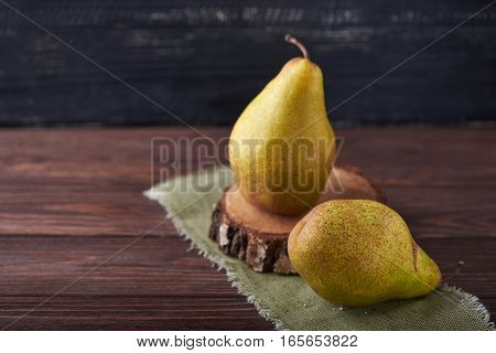 Two fresh green pears on a rustic background with napkin